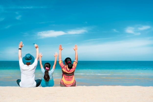 Азиатская семья сидит на пляже с белым песком и синим морем в солнечный день, концепция летнего путешествия