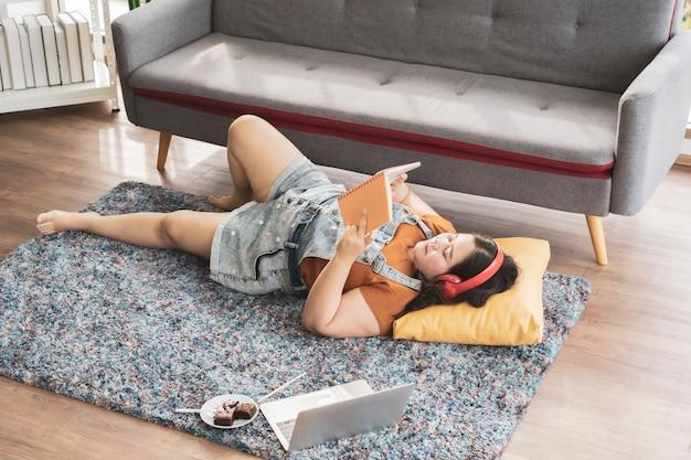 Женщина больших размеров в наушниках с компьютерным ноутбуком, лежа на ковре, читает книгу и работает дома