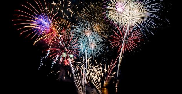 新年のお祝いのための大きな白、赤、金、青の花火の背景