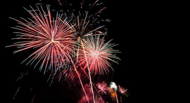 花火が美しく照らされ、黒い空を金、赤、ピンク、緑で満たした