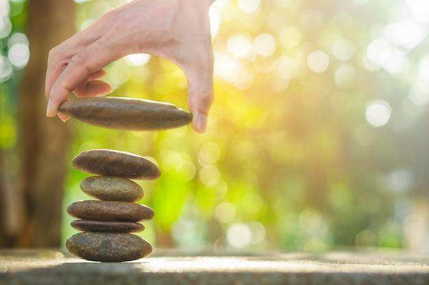 抽象的な背景のボケ味に石を持っている手とスパのバランス石