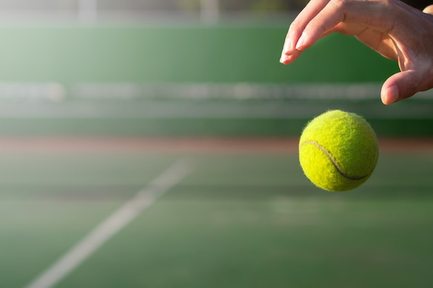 ぼかしコートの背景に手とテニスボールを閉じる