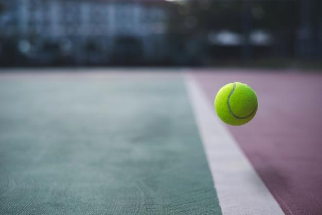 Крупным планом теннисный мяч на кортах фоне