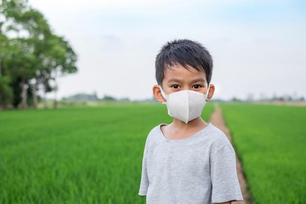 アジアの少年は、稲作で立っているフェイスマスクを着用します。健康的なコンセプト