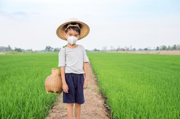 アジアの少年は、稲作農場に立っている魚のわなでフェイスマスクと竹の帽子を着用します。健康的なコンセプト