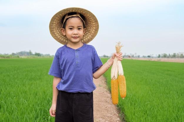 アジアの子供男の子が農場で黄色のトウモロコシを保持している竹の帽子を着用します。