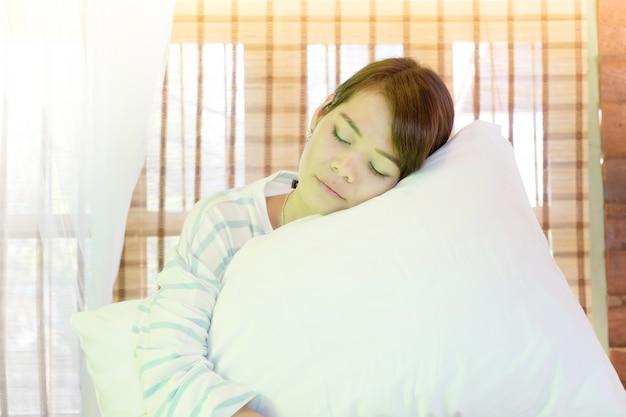 Портрет красивой азиатской молодой женщины, сидя и спать на кровати