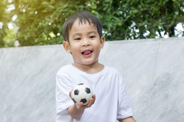 少年は発汗し、小さなサッカーのおもちゃを遊ぶことから疲れた。