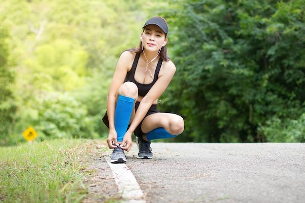 アジアの女性の着用イヤホンひざまずいて靴ひもを行うためにエクササイズトレーニングを実行した後