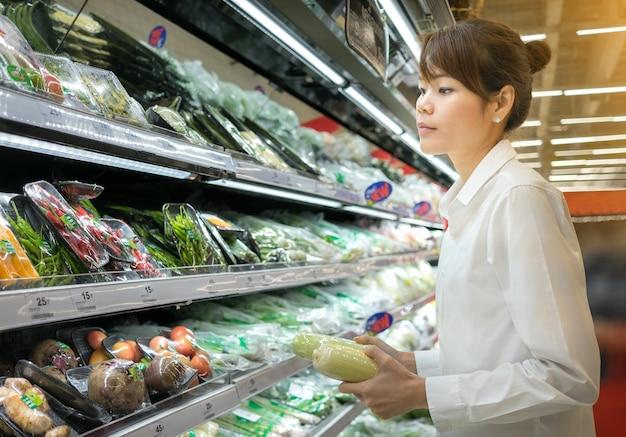 アジアの女性はスーパーマーケットで野菜を買う白いシャツを着る。