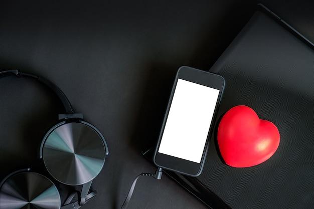 ブラックカラーガジェットのヘッドフォンスマートフォンラップトップと赤い心のトップビュー。
