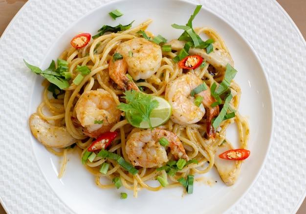 エビ、トマト、バジルのイタリアンフードスタイルでおいしいスパゲティシーフードのトップビュー