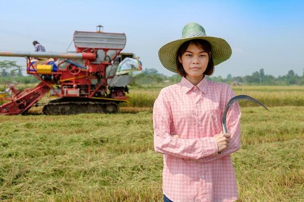 水田で田んぼを収穫するために鎌を使って帽子をかけた農夫の女性