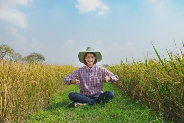 田舎の美しい田んぼのために帽子を着て親指を着て笑顔の農夫の女性。