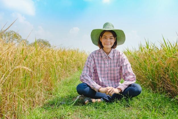 肖像画笑顔の農夫女性は、田んぼの美しい田んぼに座って帽子を着る。