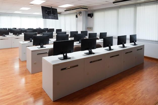 クラスルームコンピュータ。白い机の上に多くのモニターコンピュータを持つ人はいらない。