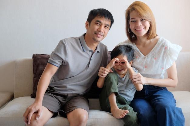 一緒にソファに座っているアジア家族の肖像画。