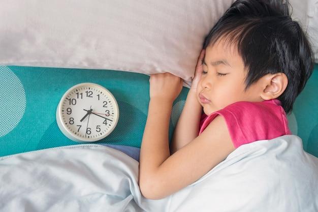 彼の頭の近くの目覚まし時計でベッドで寝ている男の子のトップビュー。眠っている少年寝てる子