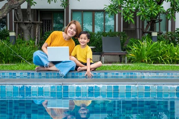 幸せなアジアの母と息子の屋外スイミングプールでラップトップを使用して