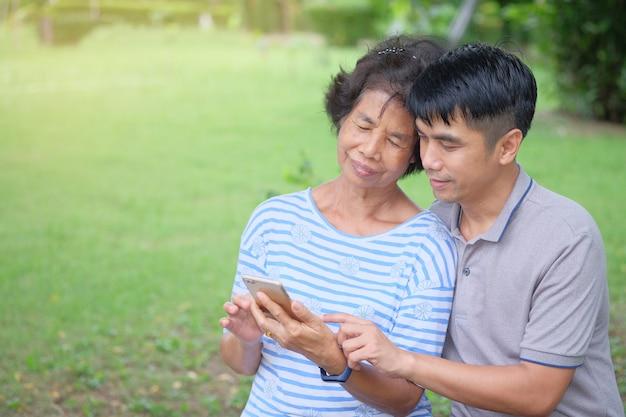 中年のアジアの母と息子スマートフォンを笑顔で見て、公園で幸せになっているのは印象的な暖かさです