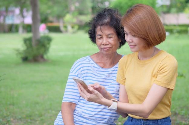 中年のアジアの母と娘笑顔でスマートフォンを見て、公園で幸せになるのは印象的な温かさです