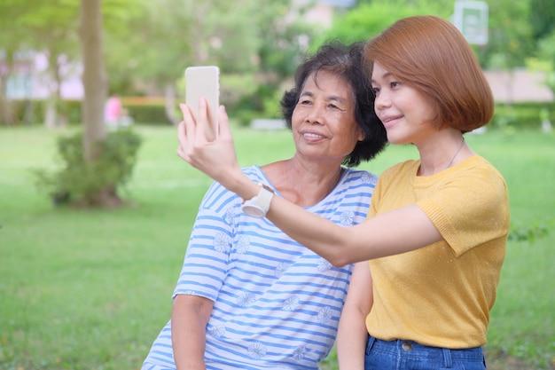 中年のアジアの母と娘がスマートフォンで自分撮りをして笑顔で公園で幸せになっているのは印象的な暖かさです