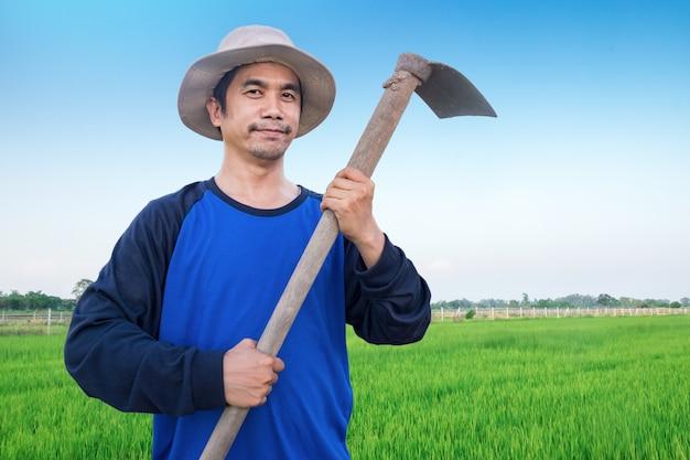 幸せなアジア人の肖像画は笑って、青いシャツを着て立っている農夫