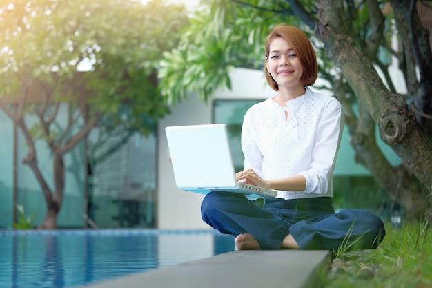 Азиатская женщина сидит, чтобы использовать ноутбук в парке
