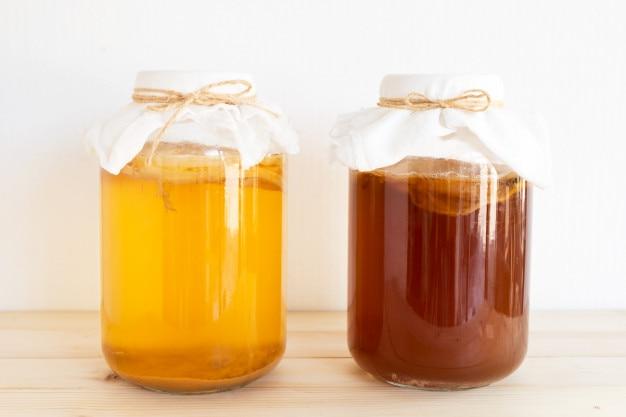 Ферментированный напиток, чай-джунг и здоровый натуральный пробиотик в виде кубики в стеклянной банке.