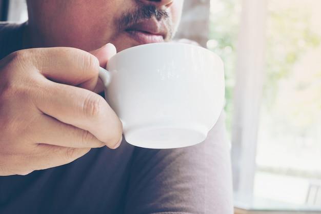 喫茶店でホットコーヒーカップを持っている男