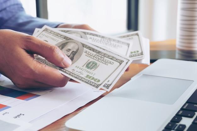 ビジネスの女性のオフィスで手でドル紙幣を保持