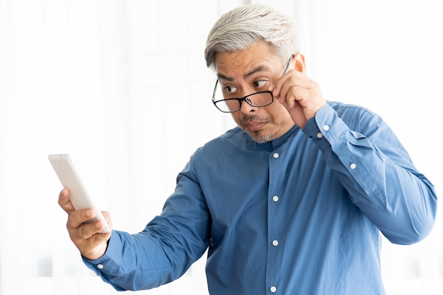 Азиатский бизнес старик с седыми волосами в очках и работает в офисе