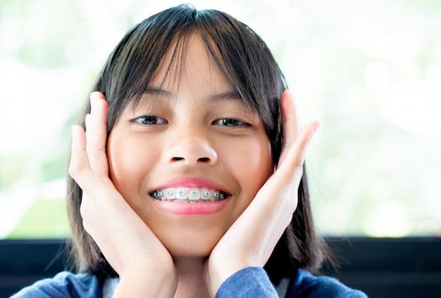 Девушка с брекеты, улыбаясь и счастливым