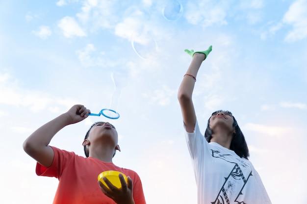Брат и девочка, пускающие мыльные пузыри на улице вместе в саду