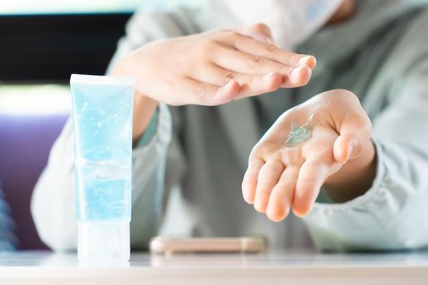 Девушка использует дезинфицирующий гель для рук или антибактериальный гель для рук, чтобы очистить ее руку