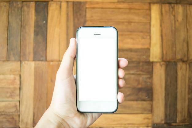 若い男は携帯電話を使ってインターネットをサーフィンしています。