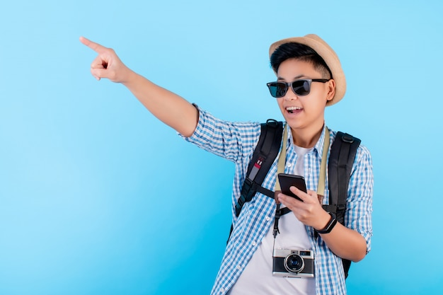 幸せそうに笑っている若いアジア人の肖像画。旅行の準備ができて、青のコピー領域を指している手を見つける