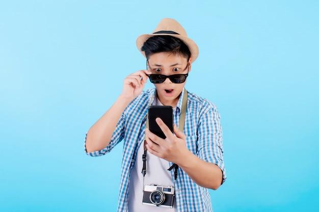 Туристы с удивлением получают поразительные новости на своих смартфонах в дороге. шокирующие азиатские туристы в летней повседневной одежде с отдельными камерами на синем фоне. путешественники за границей на отдыхе
