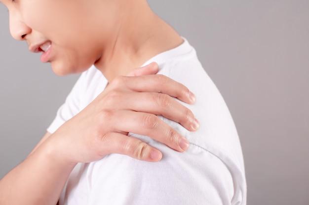 アジア人は肩の痛みに苦しんでいる白いシャツを着ています。健康概念