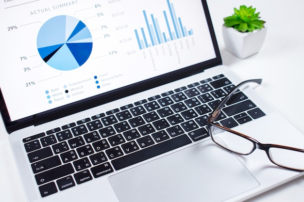 投資家はコンピュータの前面にある財務ダッシュボードを分析します。財務コンセプト。