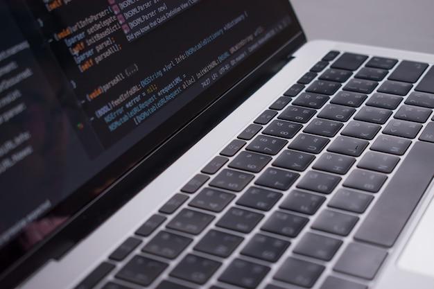 閉じる。図は、開発者がホワイトテーブル上にコンピュータモニタを作成したコードを示しています。