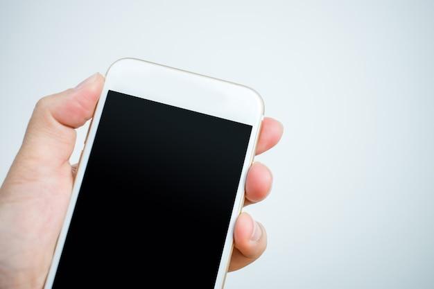 白い電話を持つ手のクローズアップショット。