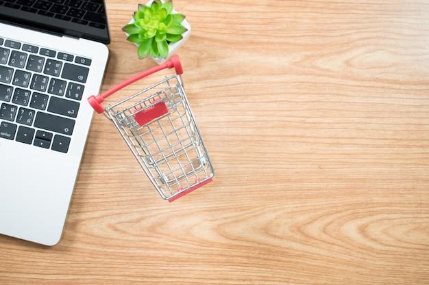 ショッピングカート、ビジネスマンのテーブル上のコンピューター。事業コンセプト