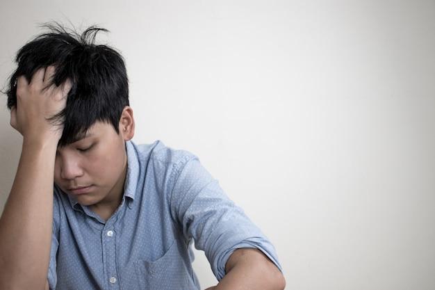 Люди грустно сидят в спальне и держатся за лоб, испытывая головную боль.