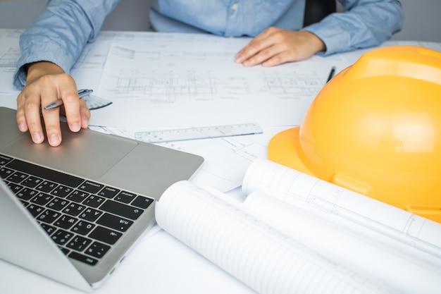 エンジニアの手が机の上に家の計画を作成していたコンピューターに取り組んで