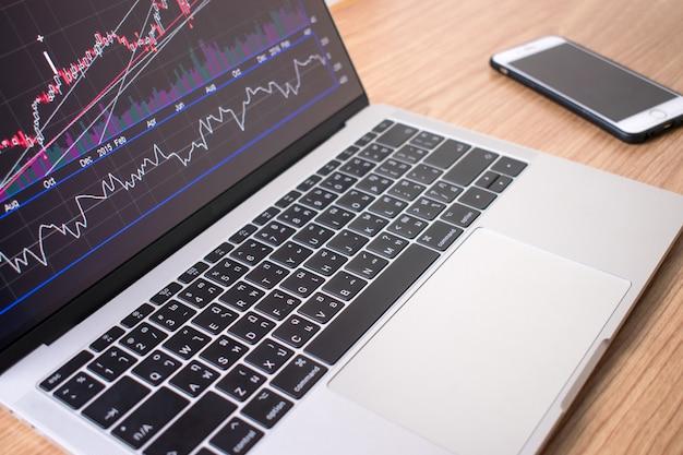 Макро-изображение ноутбука показывает данные финансового графика на деревянном столе со смартфоном с правой стороны.