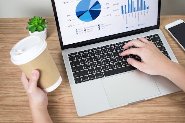 Макро фотографии бизнесменов анализируют финансовые графики на экране компьютера, одновременно выпивая кофе.