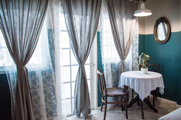 ティーテーブルは大きな窓の横にある植木鉢と日光フィルター付きの大きな灰色のカーテンでセットされています。