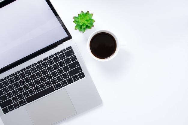 モダンなスタイルの白い机の上のコーヒーカップとラップトップコンピューターのトップビュー