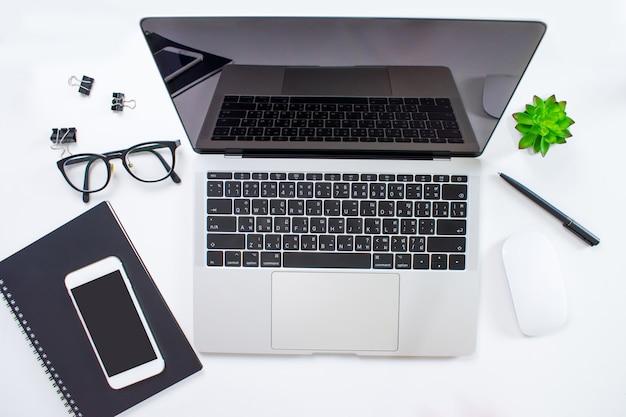 ラップトップコンピューターと作業アクセサリーのモダンな白い机の上から見る。